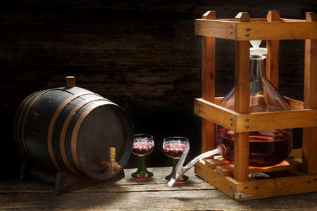 Wine balloon with red wine in a wooden rack, glasses and barrel in the wine cellar Standard-Bild