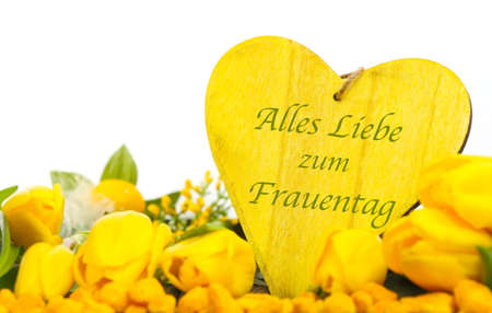 All the best for women`s day - yellow tulips and heart as a greeting card in german Standard-Bild