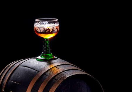 White wine glass stands on an old wooden barrel,dark background Standard-Bild