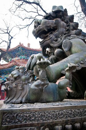 The bronze lion statue in front of Yonghe Temple also known as Palace of Peace and Harmony Lama Temple or simply Lama Temple in Beijing, China Stok Fotoğraf