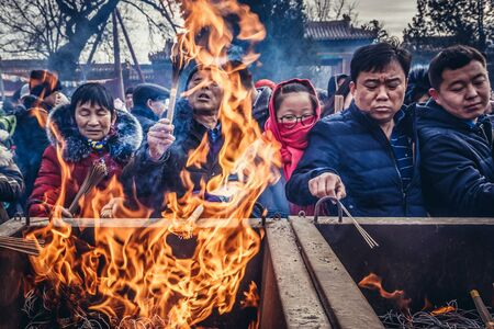 Beijing, China - February 7, 2019: Tourists burns incenses in Yonghe Temple also known as Yonghe Lamasery or Lama Temple in Beijing
