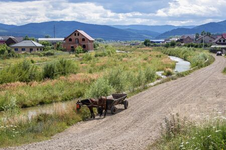 Horse drawn wagon on a road in Romanian village of Marginea, famous for the traditional handmade production of black pottery Banco de Imagens