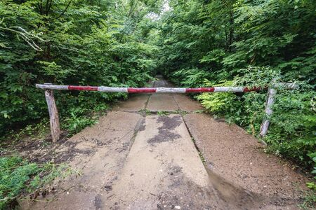 Road barrier near Object 1180 - unfinished bunker from Cold War period in Moldova 스톡 콘텐츠