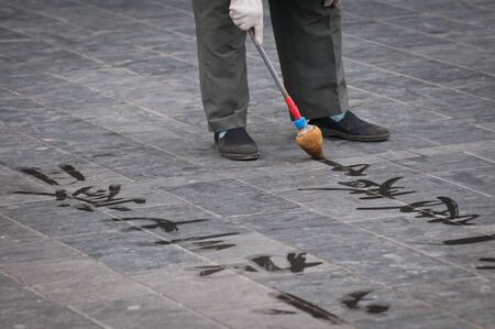 man practising chinese calligraphy near the Temple of Heaven in Beijing, China