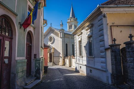 Street in historic part of Sighisoara city, Romania - view with Cathedral of Saint Joseph