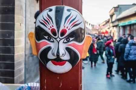 Traditional Beijing Opera Mask in front of a gift shop in Liulichang hutong, famous shopping area near Qianmen Street in Beijing city, China