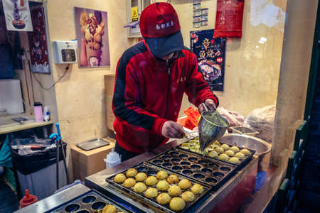 Beijing, China - February 9, 2019: Man prepares dough balls stuffed with octopus in Nanluoguxiang hutong in Beijing city