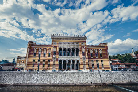 Sarajevo, Bosnia and Herzegovina - August 23, 2015. Sarajevo City Hall building commonly known as Vijecnica completed in 1896, lecated on the bank of Miljacka River
