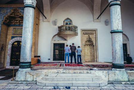 Sarajevo, Bosnia and Herzegovina - August 23, 2015. Men prays in front of 16th century Ottoman style Gazi Husrev-beg Mosque located at Bascarsija area in Sarajevo