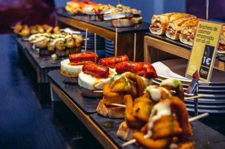 Variety of traditional Spanish snacks called pinchos in San Sebastian city also called Donostia in Gipuzkoa region of Spain