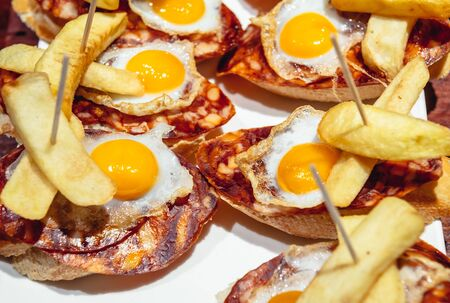 Pinchos with jamon, egg and fires - variety of traditional Spanish snacks in San Sebastian city also called Donostia in Gipuzkoa region of Spain