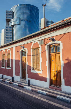 Tel Aviv, Israel - October 20, 2015. Small house and building of Trade Tower on background in historic Neve Tzedek district (lit. Abode of Justice) in southwestern part of Tel Aviv