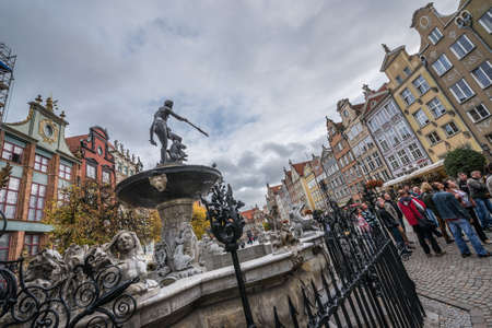 Gdansk, Poland - 17th October 2014: Tourists walks next to Neptune Fountain on Dlugi Targ Street  Long Market) on Old Town in Gdansk