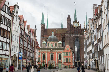 Gdansk, Poland - 17th October 2014: People at Grobla Street with King's Chapel on foreground and Basilica of the Assumption of the Blessed Virgin Mary known as St. Mary's Church in Gdansk