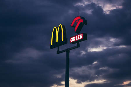 Warsaw, Poland - May 13, 2018: Logo of McDonald's and PKN Olren gas station against clouds in Warsaw city