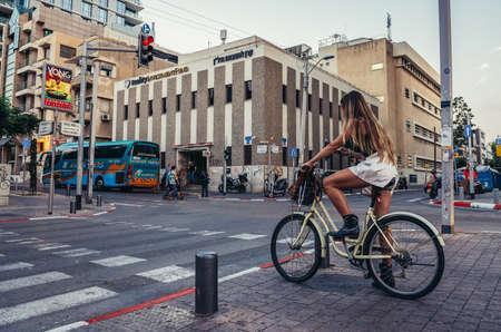 Tel Aviv, Israel - October 20, 2015. Woman rides bike at Rothschild Boulevard in Tel Aviv
