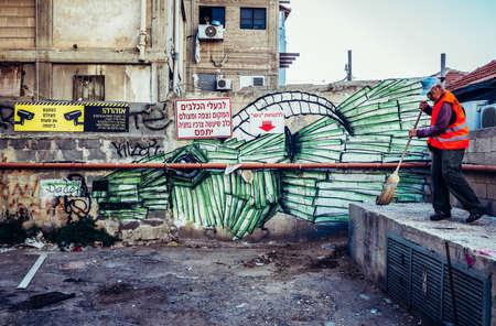 TEL AVIV, ISRAEL - OCTOBER 21, 2015. Street sweeper works in Florentin district, famous for it's graffitti street arts in Tel Aviv Editorial