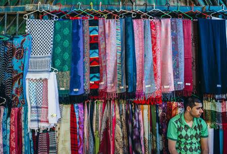 Jerusalem, Israel - October 22, 2015. Man sells textiles on Arab baazar located inside the walls of the Old City of Jerusalem