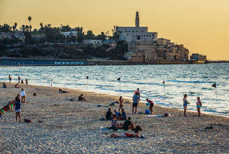 Tel Aviv, Israel - October 21, 2015. People rests on the beach. View with buildings of Jaffa also called Japho or Joppa, former port city, now part of Tel Aviv