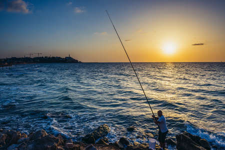 Tel Aviv, Israel - October 21, 2015. Angler fishes from the shore of the Mediterranean Sea in Tel Aviv