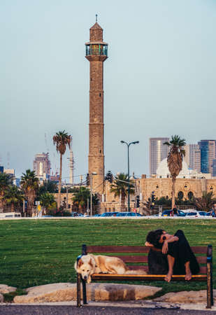 Tel Aviv, Israel - October 21, 2015. Woman with her dog rests on a bench in small park in Tel Aviv. View with Hassan Bek Mosque on background