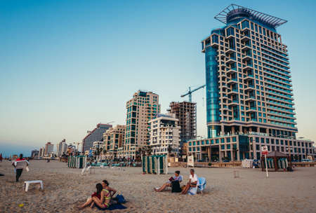 Tel Aviv, Israel - October 21, 2015. People sits on the beach in Tel Aviv. View with Sea One Tower building on the right side Editorial