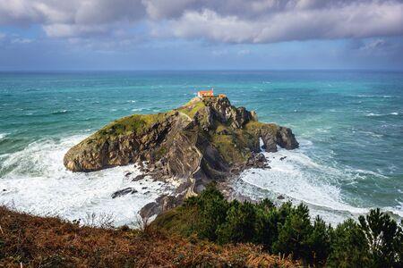 Small isle with San Juan de Gaztelugatxe hermitage on the Atlantic shore in Biscay region of Sapin