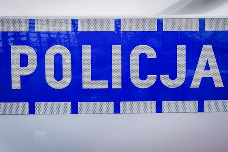 Police sign on a door of police car in Warsaw, Poland