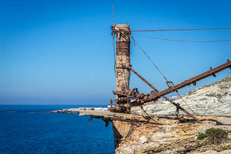Rusty old crane on the Mediterranean coast in Beirut, capital city of Lebanon, next to famous Raouche Rocks