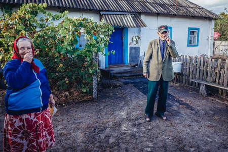 Kupuvate, Ukraine - September 21, 2016: Self settlers in front of their house in Kupovate village located in Chernobyl exclusion area