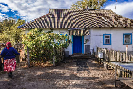 Kupuvate, Ukraine - September 21, 2016: Self settler woman in front of her house in Kupovate village located in Chernobyl exclusion area