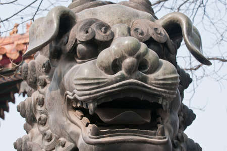 The bronze lion statue in front of Yonghe Temple also known as Palace of Peace and Harmony Lama Temple or simply Lama Temple in Beijing, China