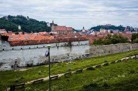 Old walls with Black Church on background in Brasov city in Romania