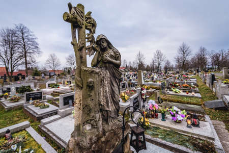 Broumov, Czech Republic - March 24, 2019: Grave sculpture in front of historic wooden Church of Virgin Mary in Broumov city
