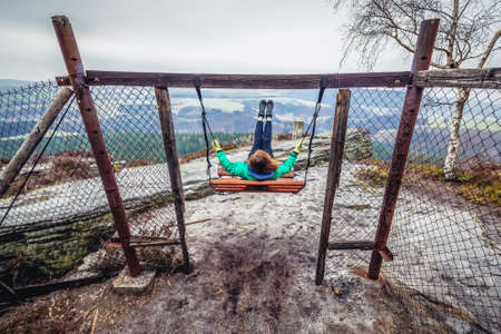Ostas Mount, Czech Republic - March 24, 2019: Tourist swings on the top of Mount Ostas reserve in Table Mountains, part of Broumovsko protected area