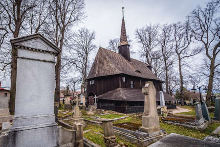 Broumov, Czech Republic - March 24, 2019: Rear view of historic wooden Church of Virgin Mary on a cemetery in Broumov city 新闻类图片