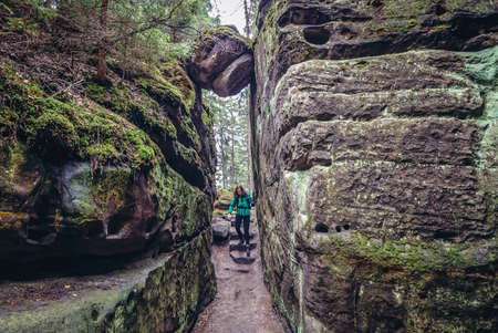 Ostas Mount, Czech Republic - March 24, 2019: Tourist in rock labirynth in Mount Ostas reserve in Table Mountains, part of Broumovsko protected area