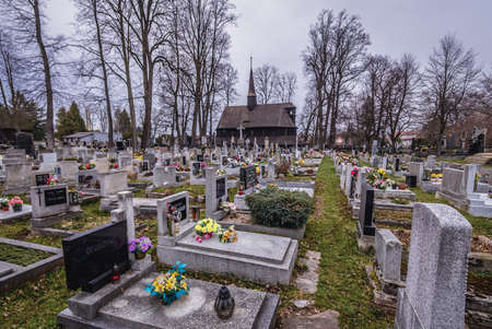 Broumov, Czech Republic - March 24, 2019: Graves on a cemetery around historic wooden Church of Virgin Mary in Broumov city 新闻类图片