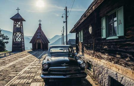 Drvengrad, Serbia - August 28, 2015. Old Volga car in front of wooden house of Drvengrad village built by Emir Kusturica