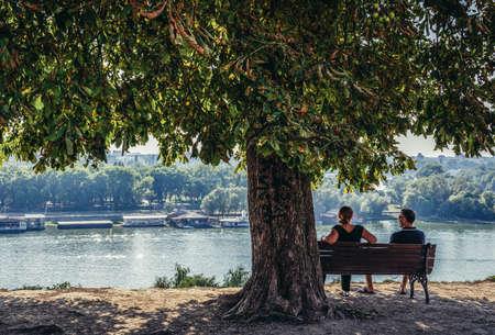 Belgrade, Serbia - August 29, 2015. Couple sits on a banch on promenade in Large Kalemegdan Park 新闻类图片