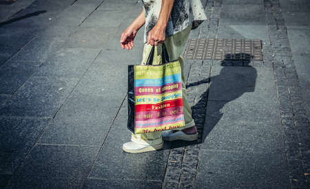 Belgrade, Serbia - August 29, 2015. Old woman walks with shopping bag on Prince Michael Street in Belgrade city