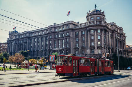 Belgrade, Serbia - August 29, 2015. Red tram car on the street in Belgrade. View with building of Serbian Ministry of Foreign Affairs 新闻类图片
