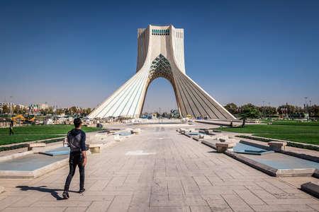 Tehran, Iran - October 15, 2016: Man walks in front at Azadi Square with Azadi Tower in Tehran Editorial