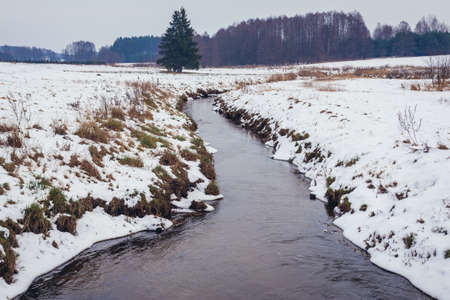 Winter scenery near Soce village, Podlasie region of Poland. View with small Rudnia river