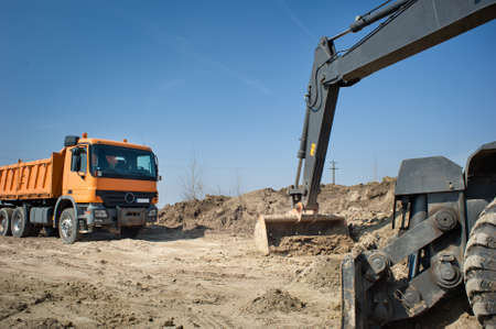 Hydraulic excavator and truck at work. photo