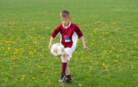kids  soccer: kid Juggling ball on the sports field