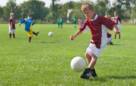soccer kick: boy kicking football on the sports field Stock Photo