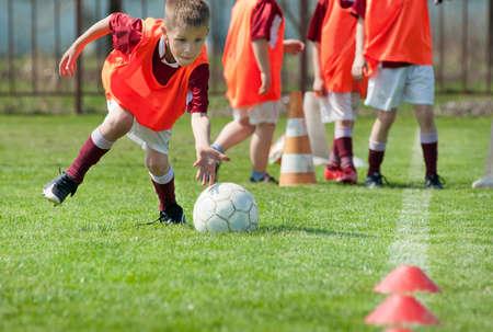 cancha de futbol: ni�o jugando con una pelota en la cancha de f�tbol