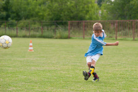 Little Boy playing soccer on the sports field photo