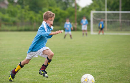 soccer kick: Little Boy playing soccer on the sports field Stock Photo